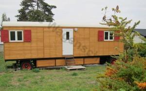 Der Bauwagen im Garten, gsäumt von zarten Büschen.