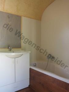 Waschbecken mit Unterschrank, Badewanne mit HPL Wandverkleidung.