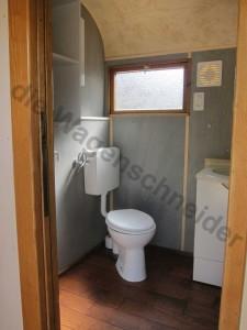 Bad mit WC, Lavabo und Wandverkleidung grau geölt.