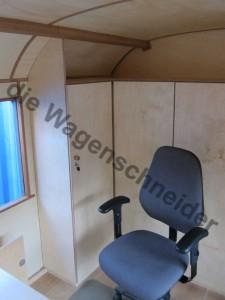 Büro mit Schreibtisch, Einbauschränken und Kurbelfenster.