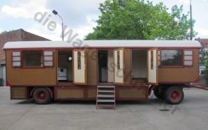 Alter Schindelwagen mit drei geöffneten Bleiglastüren im Zirkuswagen..
